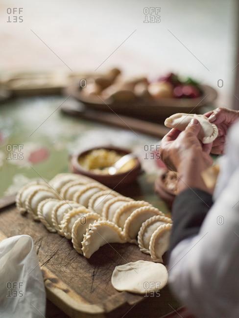 A woman forms empanadas