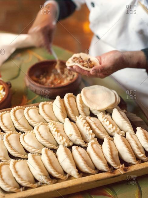 A woman fills empanadas