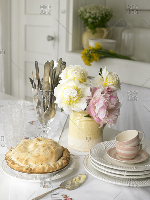 A chicken pot pie sits on a table with serving ware