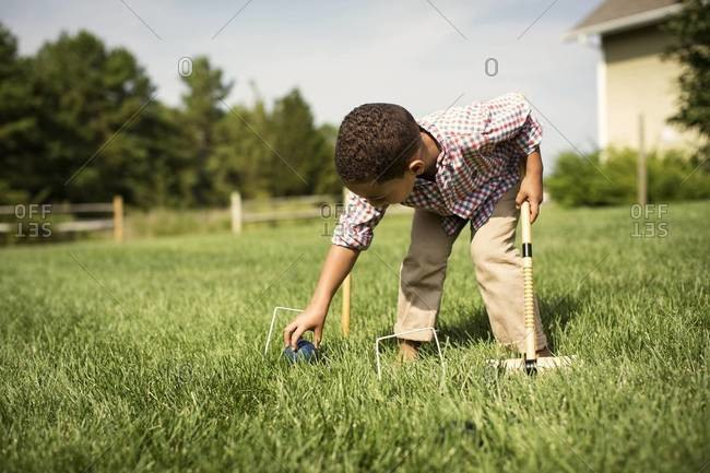 A boy sets his croquet ball