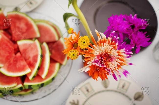 Watermelon and flowers on picnic table