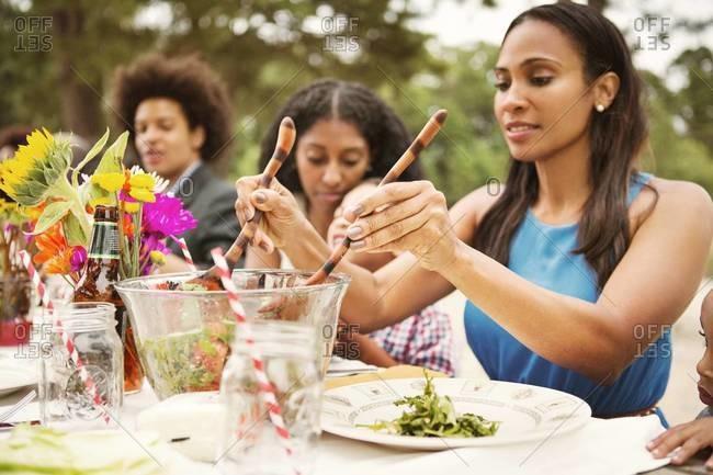 Woman serving salad at family picnic