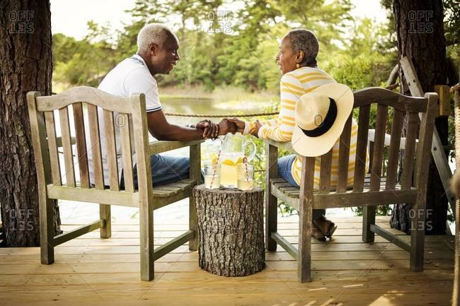 Older couple on deck holding hands