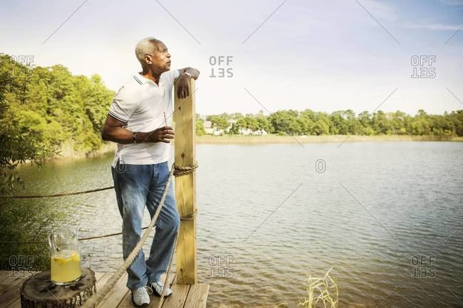 Man on dock with lemonade gazing out