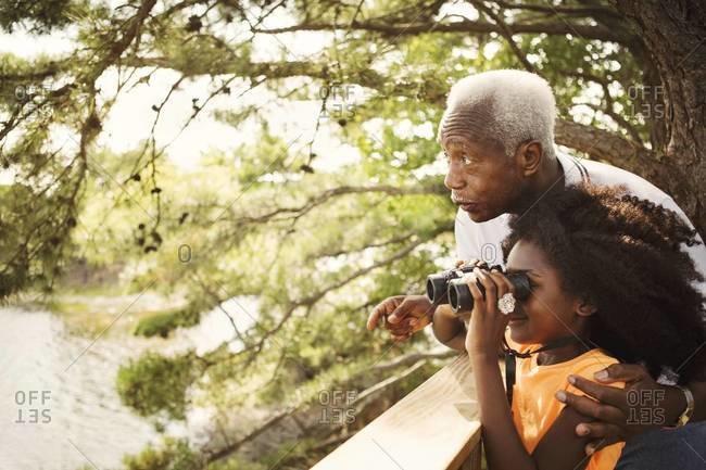 Man and girl with binoculars near lake