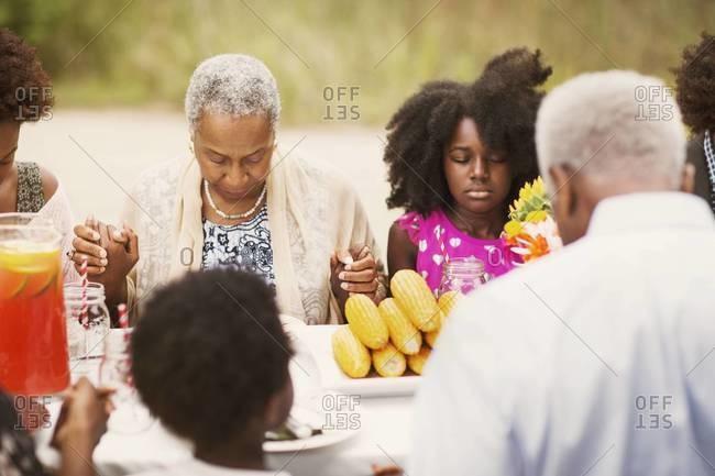 Family in prayer before picnic