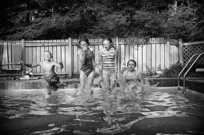 A group of kids jump into a pool