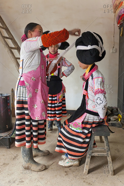Sugao, China - January 30, 2012: Long Horn Miao woman preparing the headdress of a girl