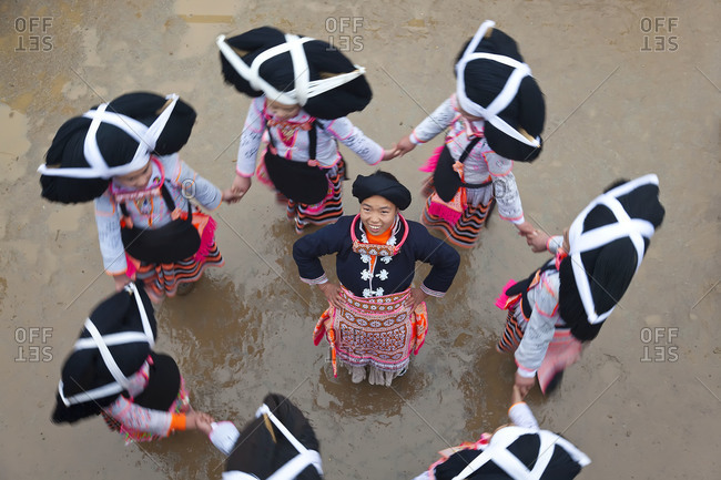 Sugao, China - January 31, 2012: Long Horn Miao children dancing in a circle
