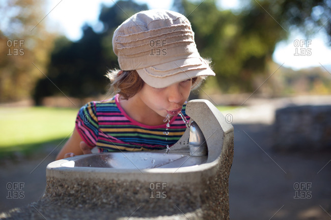 Portrait of a thirsty girl at a drinking fountain