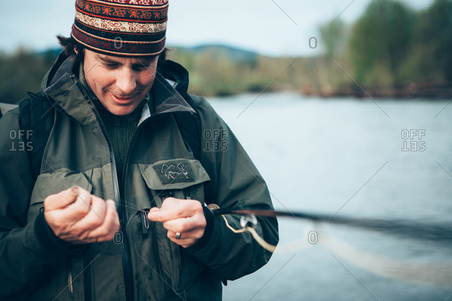 Close up of man fly-fishing, tying hook to line, Hoh River in background, Olympic NP, WA, USA
