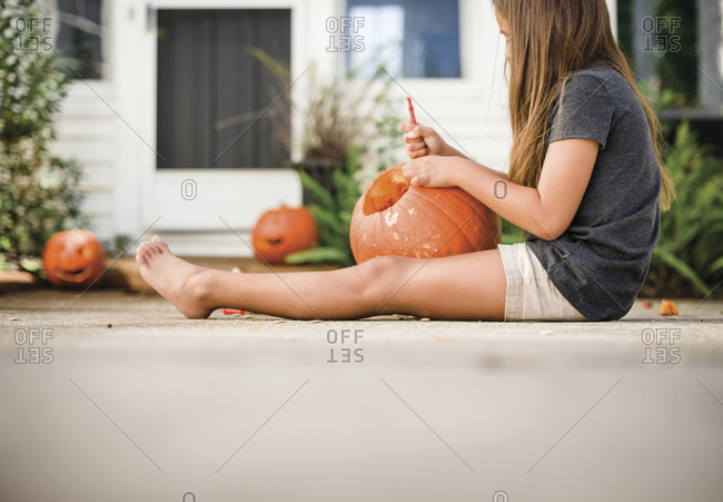 Girl carving a pumpkin for Halloween