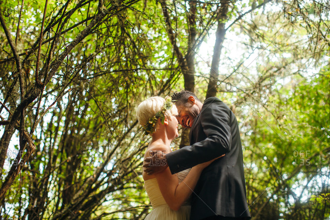 Newlyweds hugging in a forest