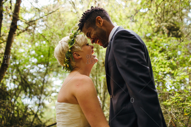 Young couple laughing in a forest on their wedding day