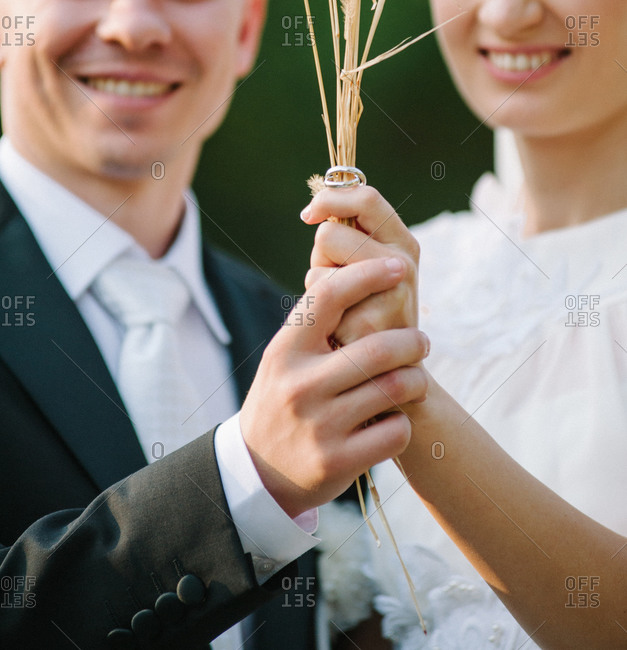 Newlywed couple holding the wedding rings on wheat straws
