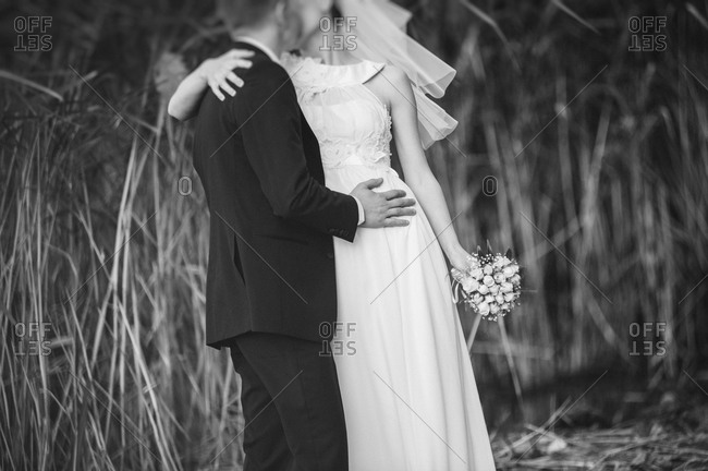 Newlyweds kissing in a wheat field