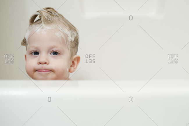 Child in bath with shampoo in hair