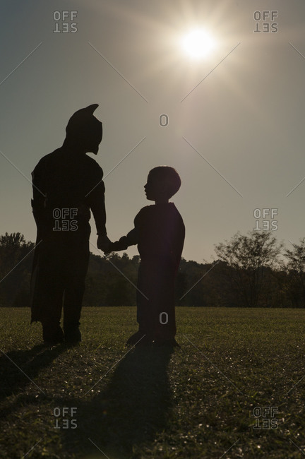 Two boys in costume silhouetted by sun