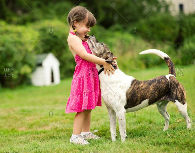 Girl hugging her dog in the garden