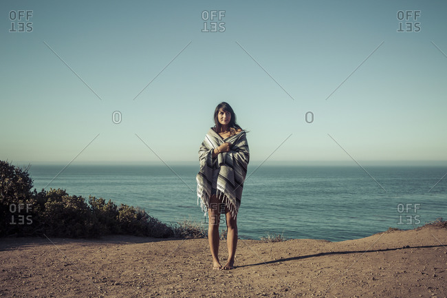 Young woman covered with a blanket on a coast