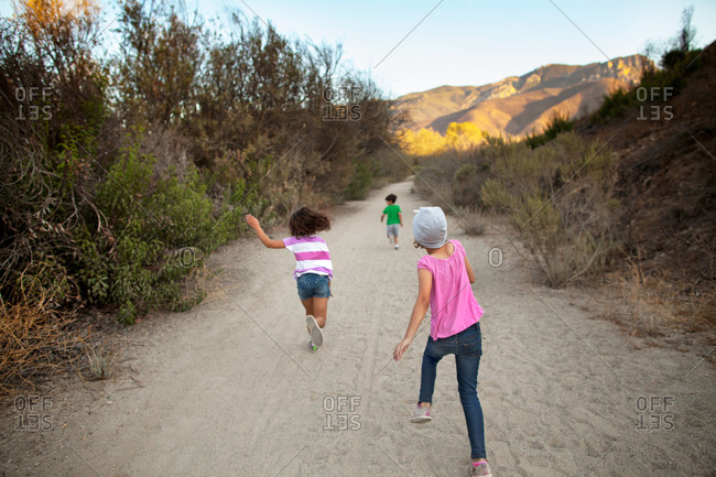 Three kids running up rugged trail