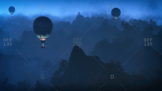 Balloons flying over mountain landscape at night