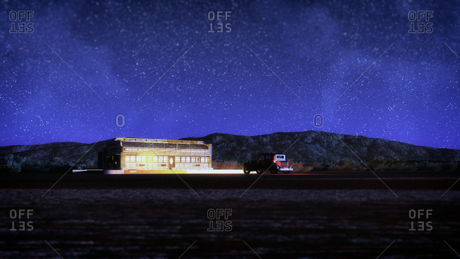Desert landscape with desolate diner and vintage car at night