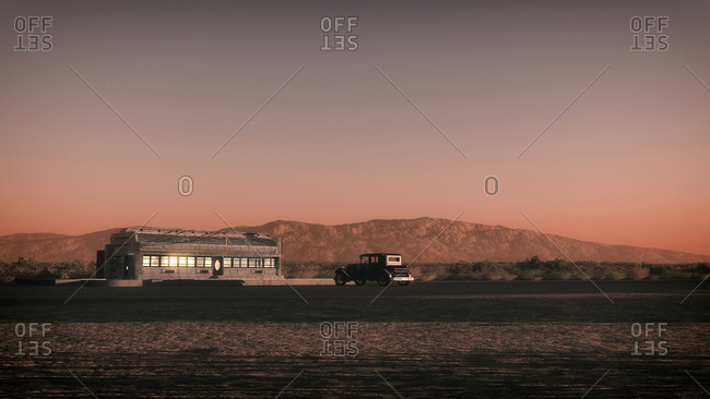 Desert landscape with desolate diner and vintage car at sunset