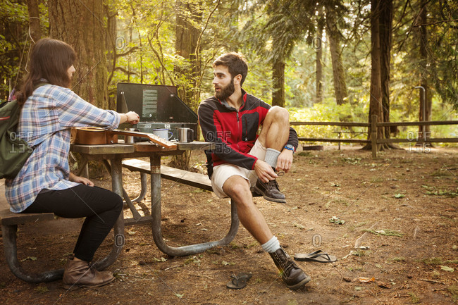 Couple sitting at a picnic table in a forest