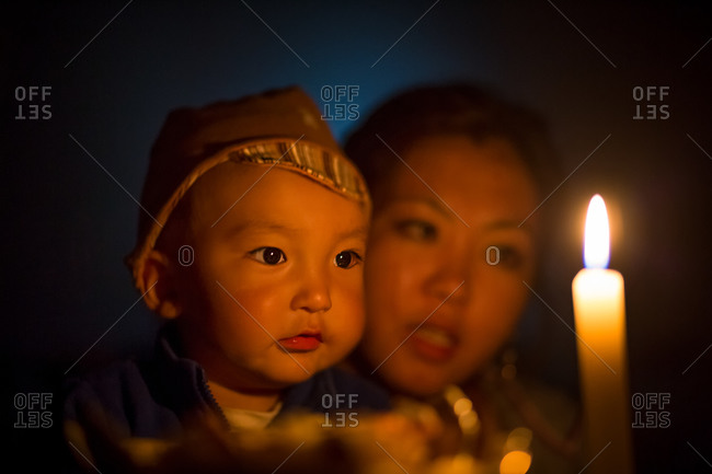 Bokonbayevo, Issyk Kul Province, Kyrgyzstan - August 15, 2014: Kyrgyz Woman and Child in the Light of a Candle, Kyrgyzstan