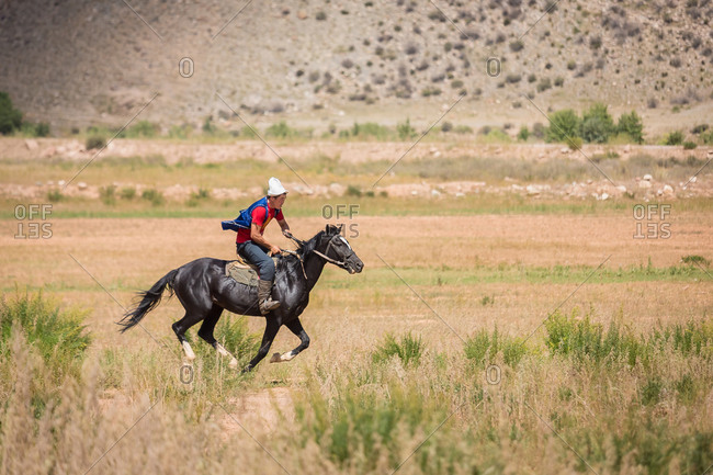 Kizil-Oi, Suusamyr Valley, Kyrgyzstan - August 23, 2014: Kyrgyz Rider on a Black Horse During a Nomadic Games Festival, Kyrgyzstan