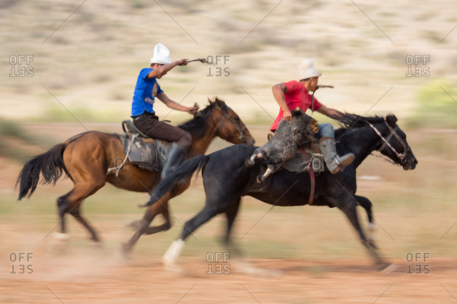 Kizil-Oi, Suusamyr Valley, Kyrgyzstan - August 23, 2014: Two Buzkashi Players Riding Towards the Goal During a Nomadic Games Festival, Kyrgyzstan