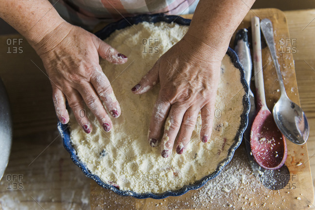 Woman patting crumble mixture into a pie dish, making a fruit crumble pudding