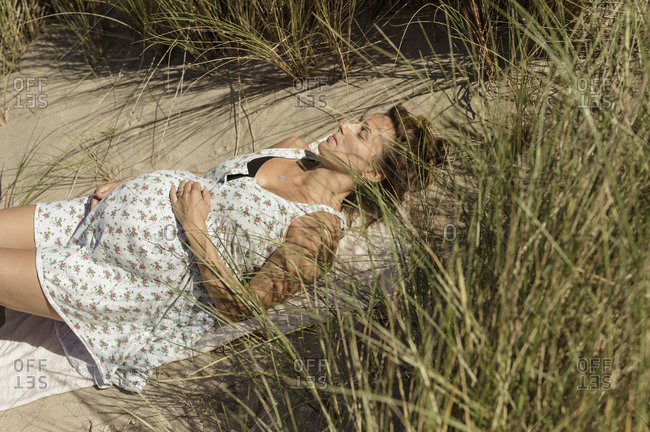 A pregnant woman lying in the sun in the sand dunes