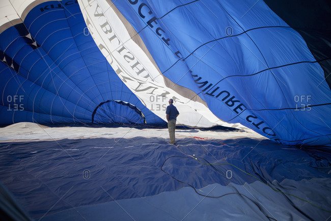 Man standing inside a partially inflated hot air balloon