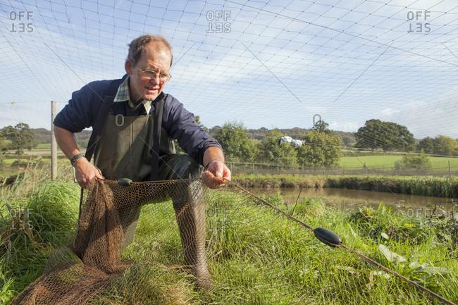 A man handling a large net, pulling it across water