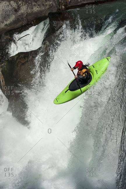 Man whitewater rafting on waterfall