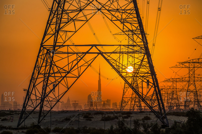 Transmission towers at sunset with Dubai skyline in the background