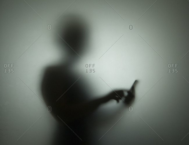 A silhouette of a woman with a phone
