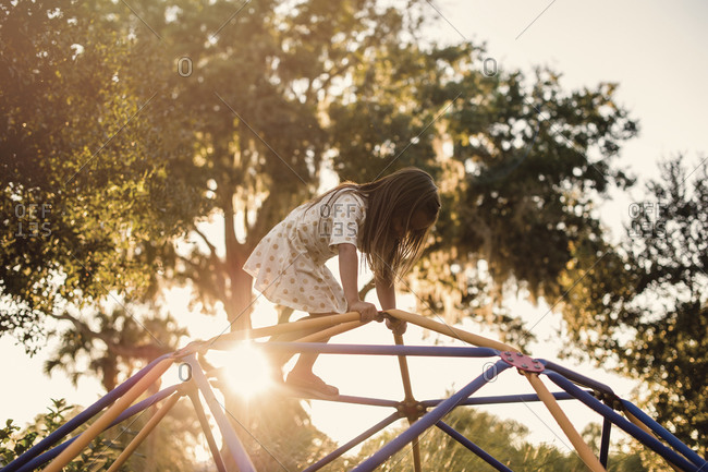 Young girl climbing on a jungle gym at a playground