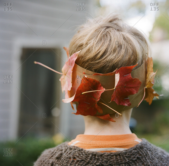 A young boy wears a leaf crown