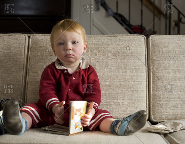 A toddler sits on a couch