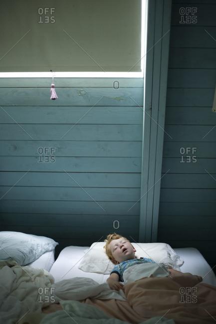 A little boy sleeps on the floor