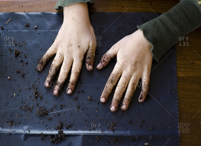 A boy displays his dirty hands on a piece of plastic