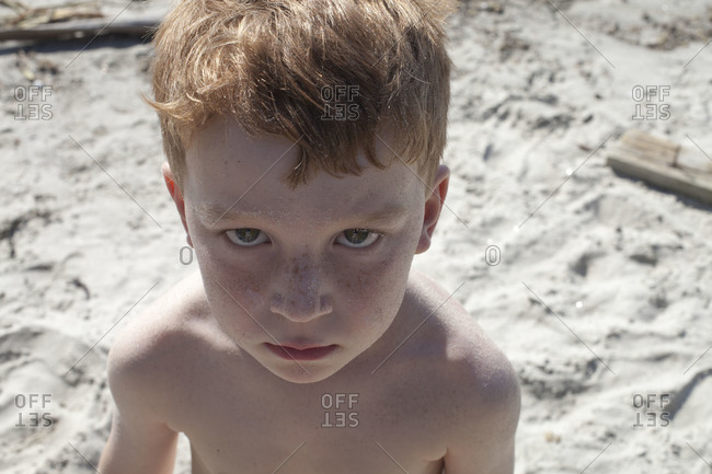 Angery boy at the beach with sand on his face