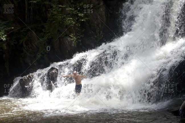 A man frolics in a waterfall