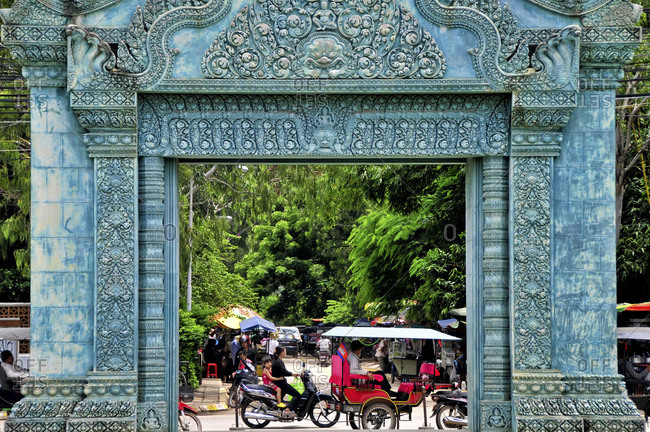 Siem Reap, Cambodia - September 14, 2012: Traffic passing Ornate gate