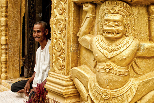 Phnom Sampeau, Cambodia - September 19, 2012: Smiling man sitting at the entrance of a temple