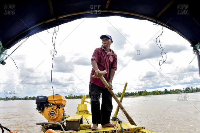 Cambodia - September 27, 2012: Man paddling a boat on the Mekong river
