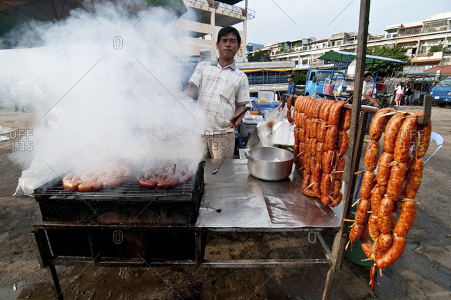 Phnom Penh, Cambodia - October 1, 2012: Man frying sausages in the Russian market